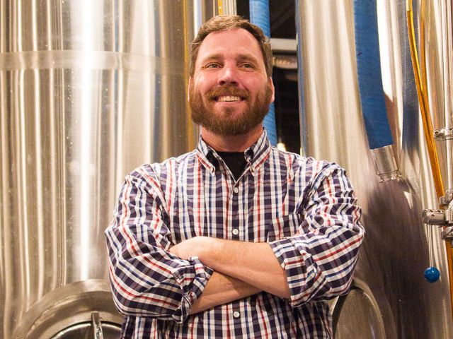 Co-owner Shawn Phillips stands in front of beer tanks at Spencer Devon Brewing.