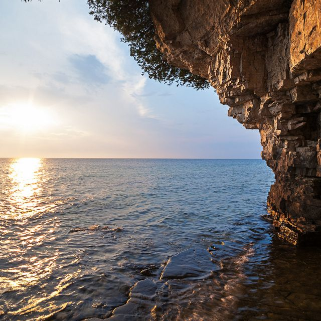 The sun shines over water and a rock formation.