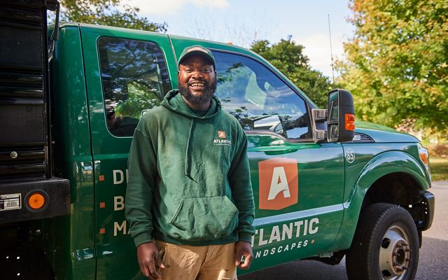 Stephen Smith pauses during his work day to pose with a smile in front of his green landscaping truck.