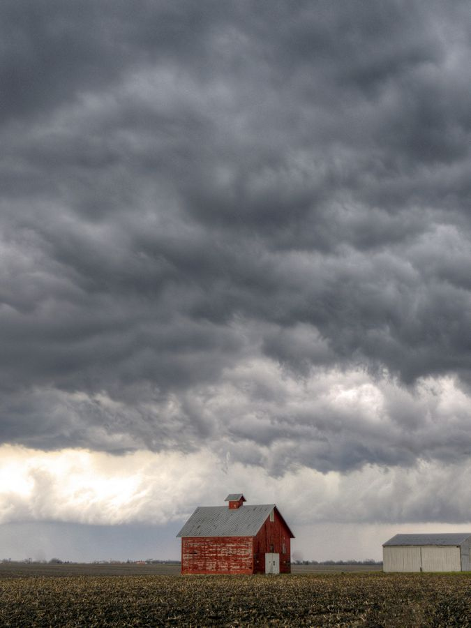 Storm clouds gather above a farm field.