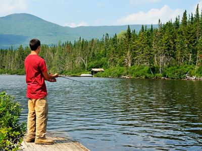 A man in a red shirt fishing in a pond.