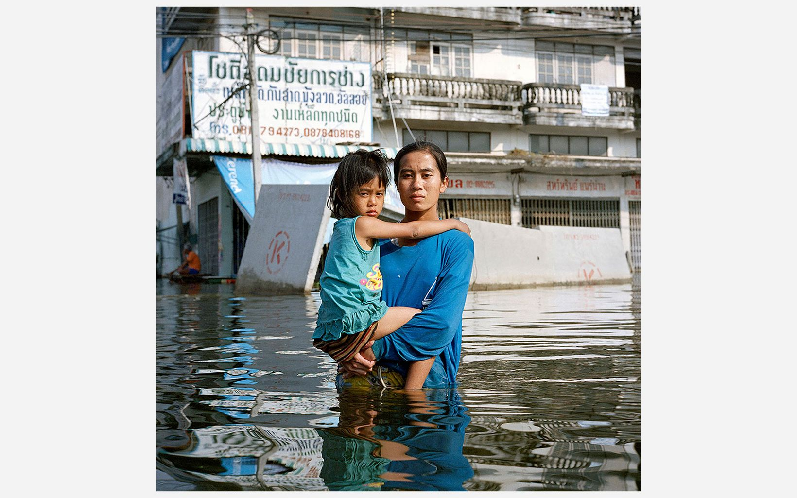 Anchalee Koyama holds her daughter over deep floodwater in the Taweewattana district of Bangkok, Thailand