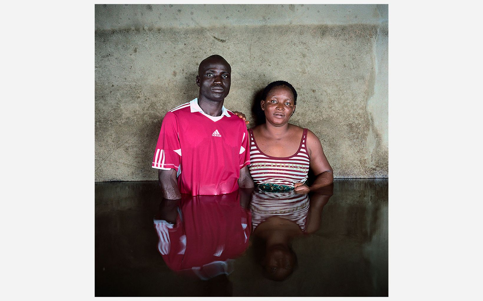 Kingsley Isiakpere and Edna Silas stand in waist deep water in the state of Bayelsa in Nigeria