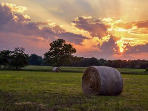 The sun rises over Illinois farm fields and bales of hay.
