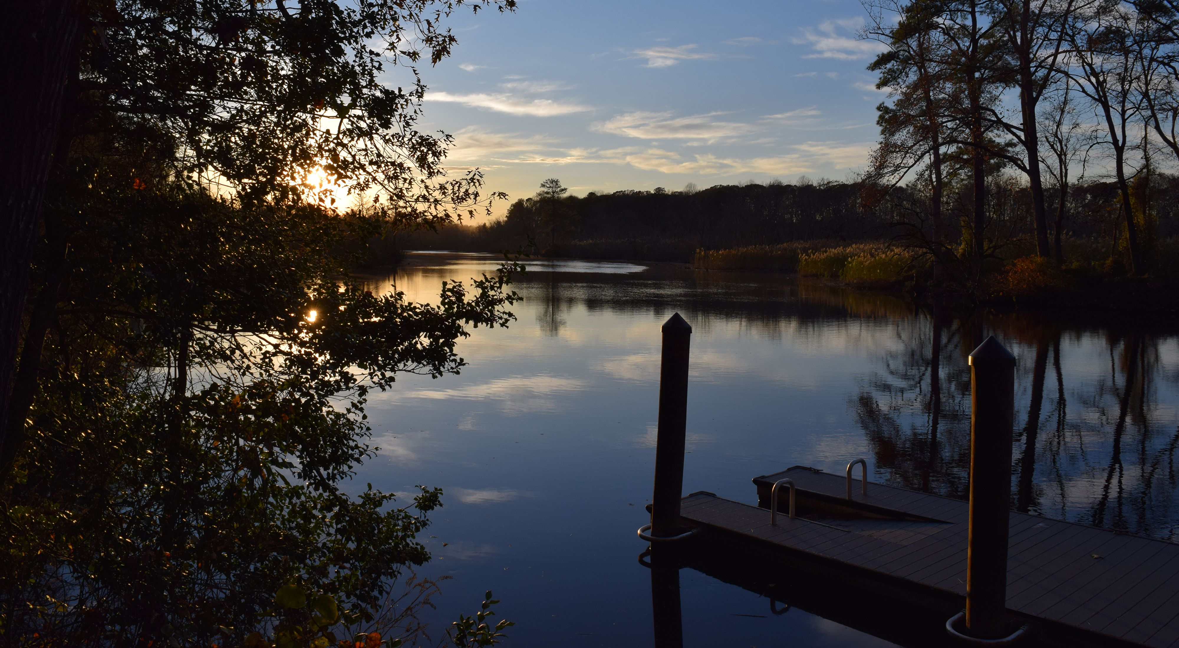 Sunset on the Broadkill River. The sun is low on the horizon, hidden by trees. The trees that line the river are in deep shadow. The still water reflects the clouds in the sky above.