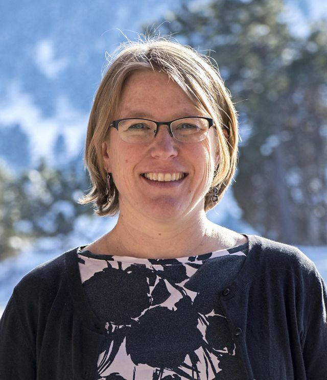 Headshot of Coastal Science Program Manager Susan Bates. A smiling woman wearing a navy blue cardigan stands in front of a blue sky and a tree with green leaves.