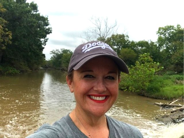 Portrait of a woman wearing a hat standing in front of a river.