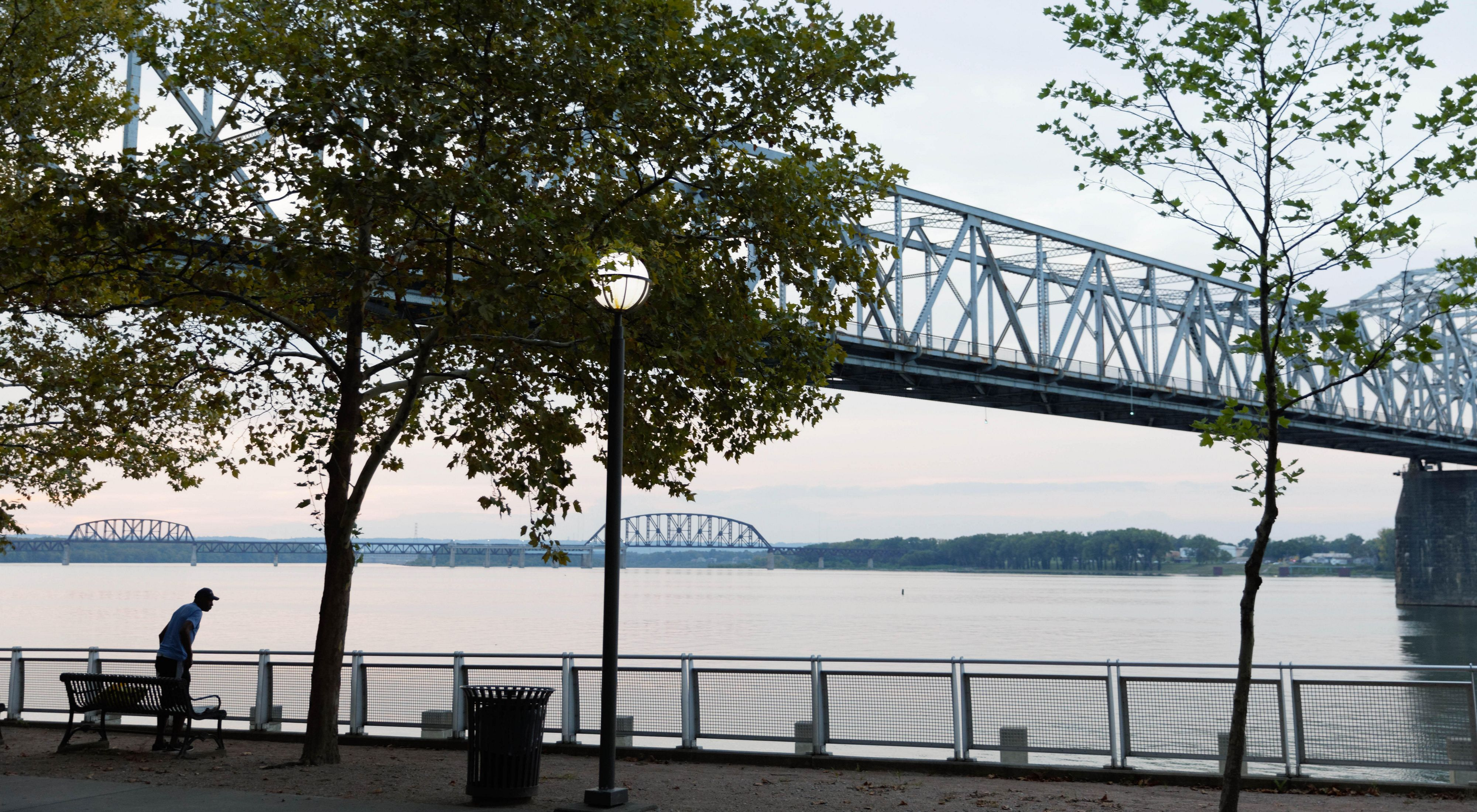 Photo of a steel bridge crossing the Ohio River, with a riverside park in the foreground.