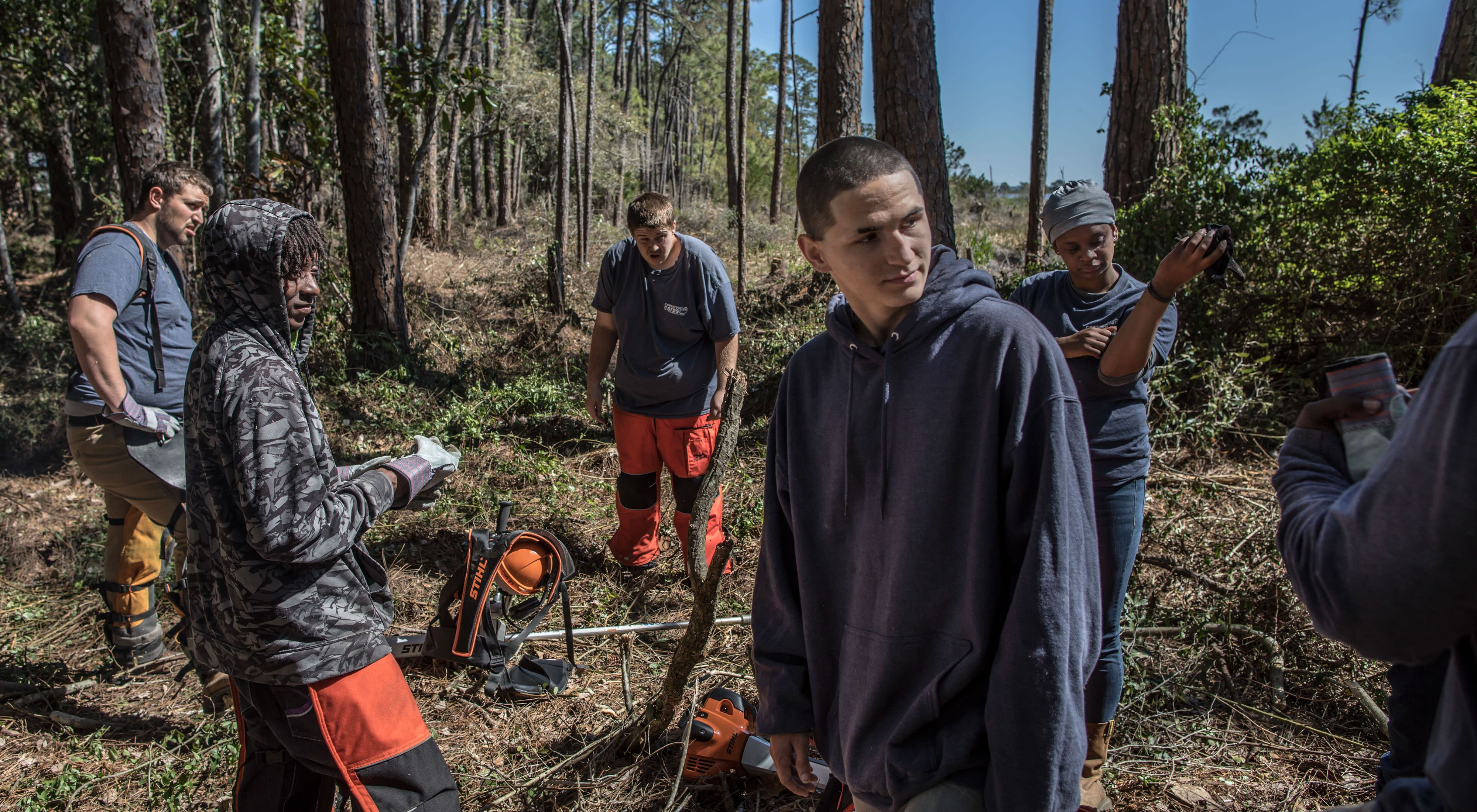 A group of young people with chainsaws and other equipment on a break in a wooded area.