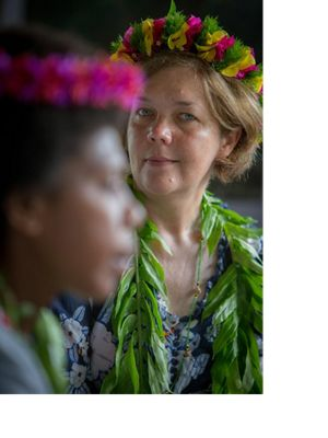 Woman wearing lei looks on in the background as woman speaks in foreground