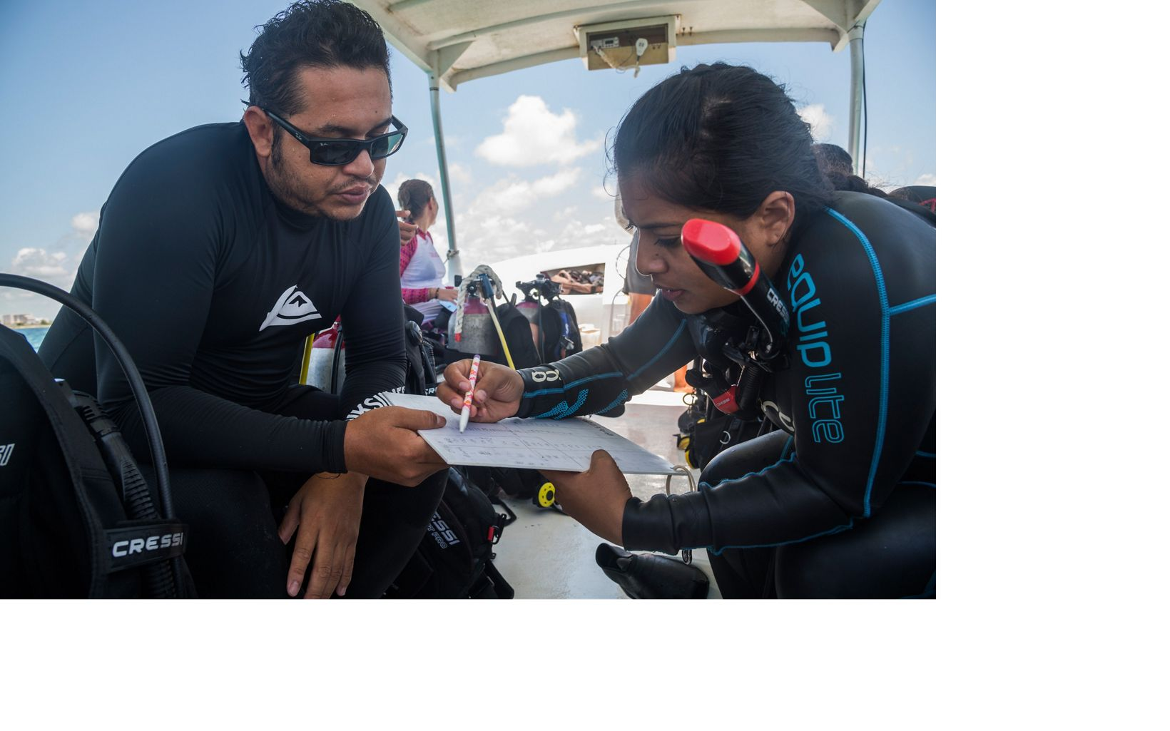Two divers sit on a boat and work together over a paper on a clipboard.