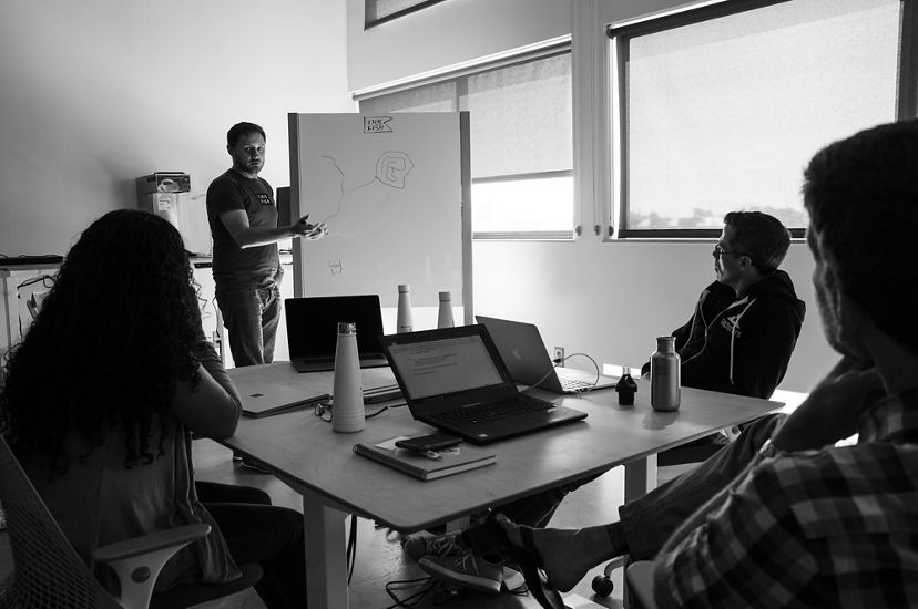 A man stand next to a whiteboard, gesturing toward the simple drawing on it, while others look on