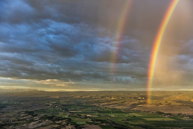 a wide view of rolling hills of developed land against a cloudy sky with two rainbows illuminated to the right of the shot.