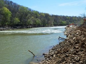 A river flows past loose rocks and digging equipment.