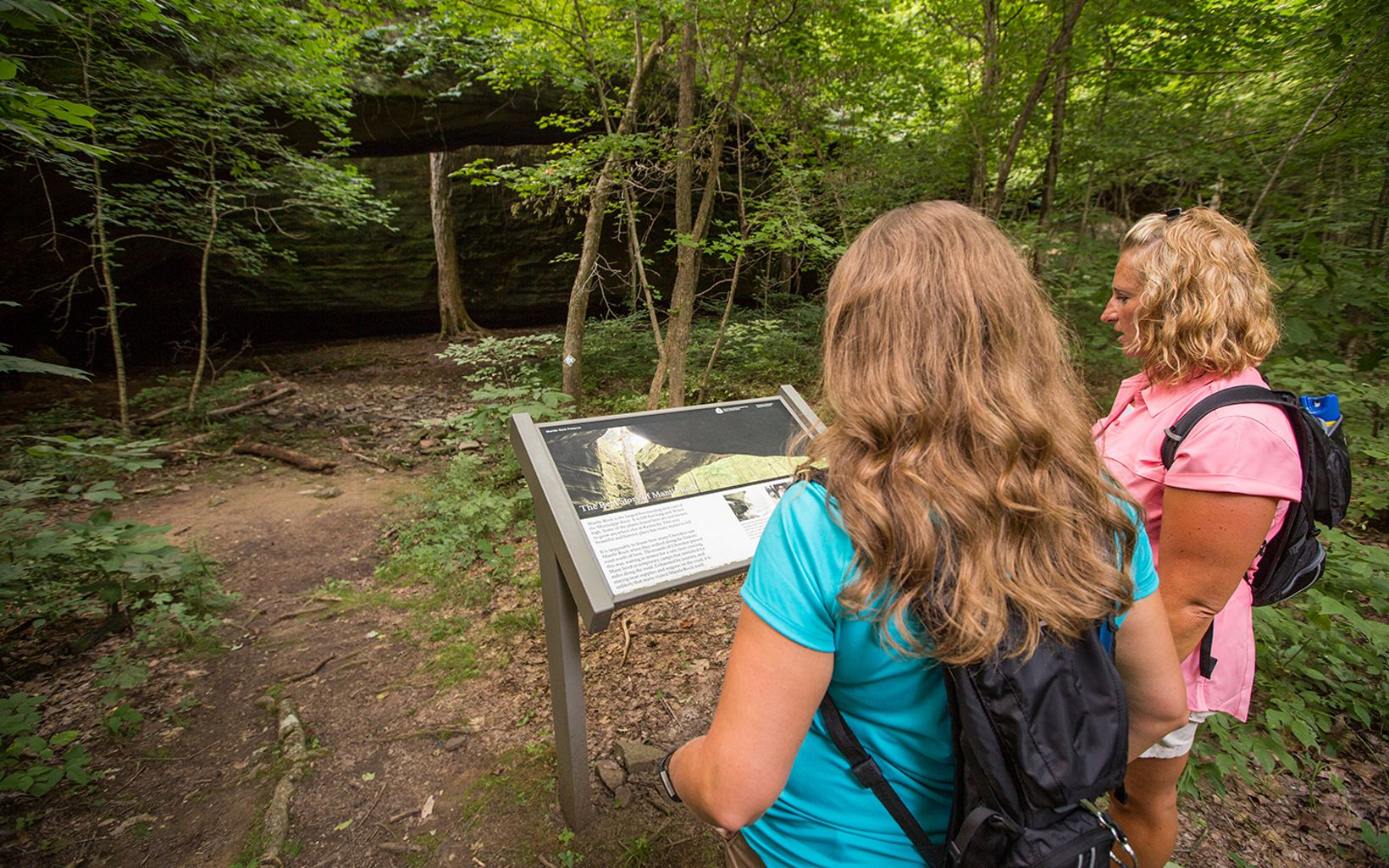 Two hikers read an interpretive sign on a hiking trail.