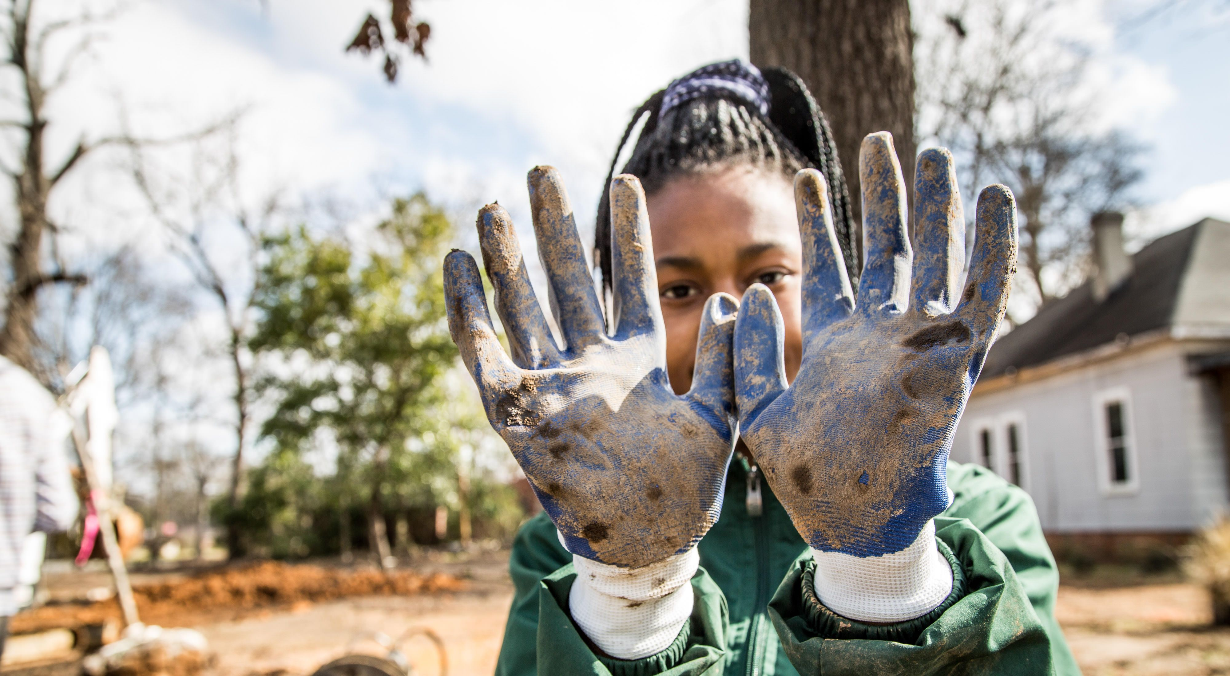 A young girl holds her gloved hands up to show off the dirt she got on them plantin trees