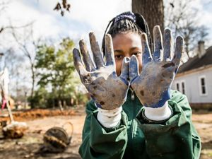 A nature lab participant hold up muddy, gloved hands.