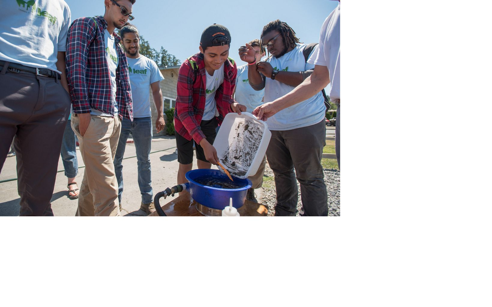 interns pouring sand into bucket