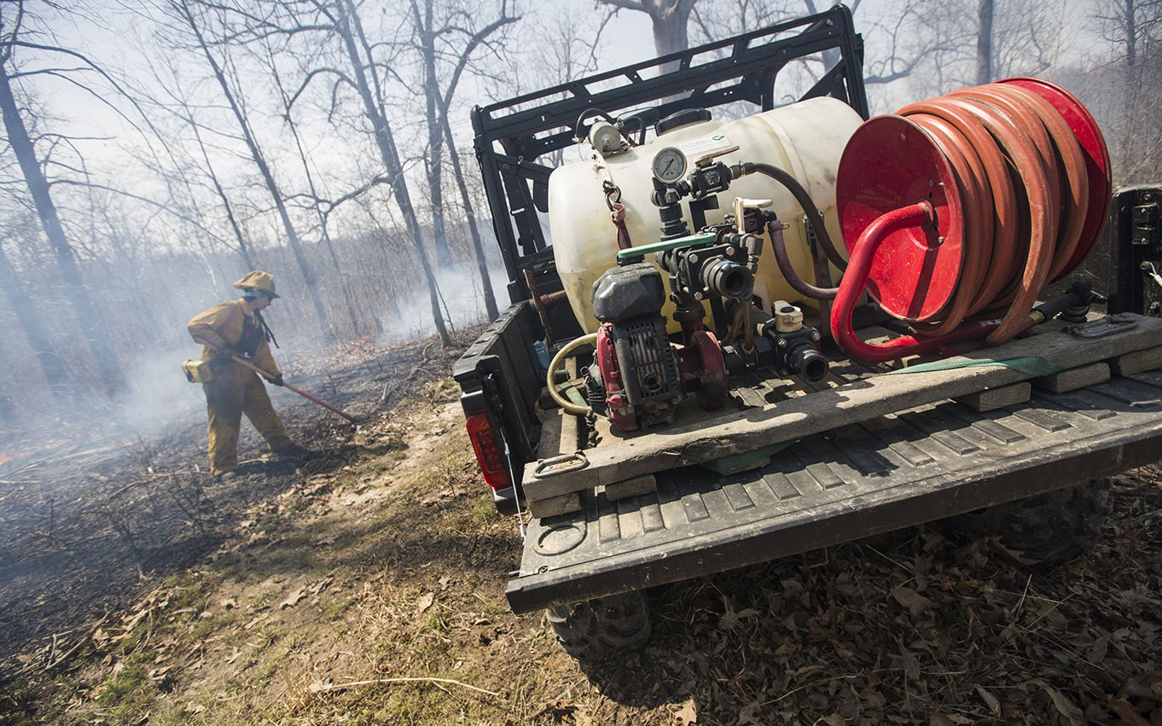 Fire personnel rakes a burned area after a fire next to a water truck.