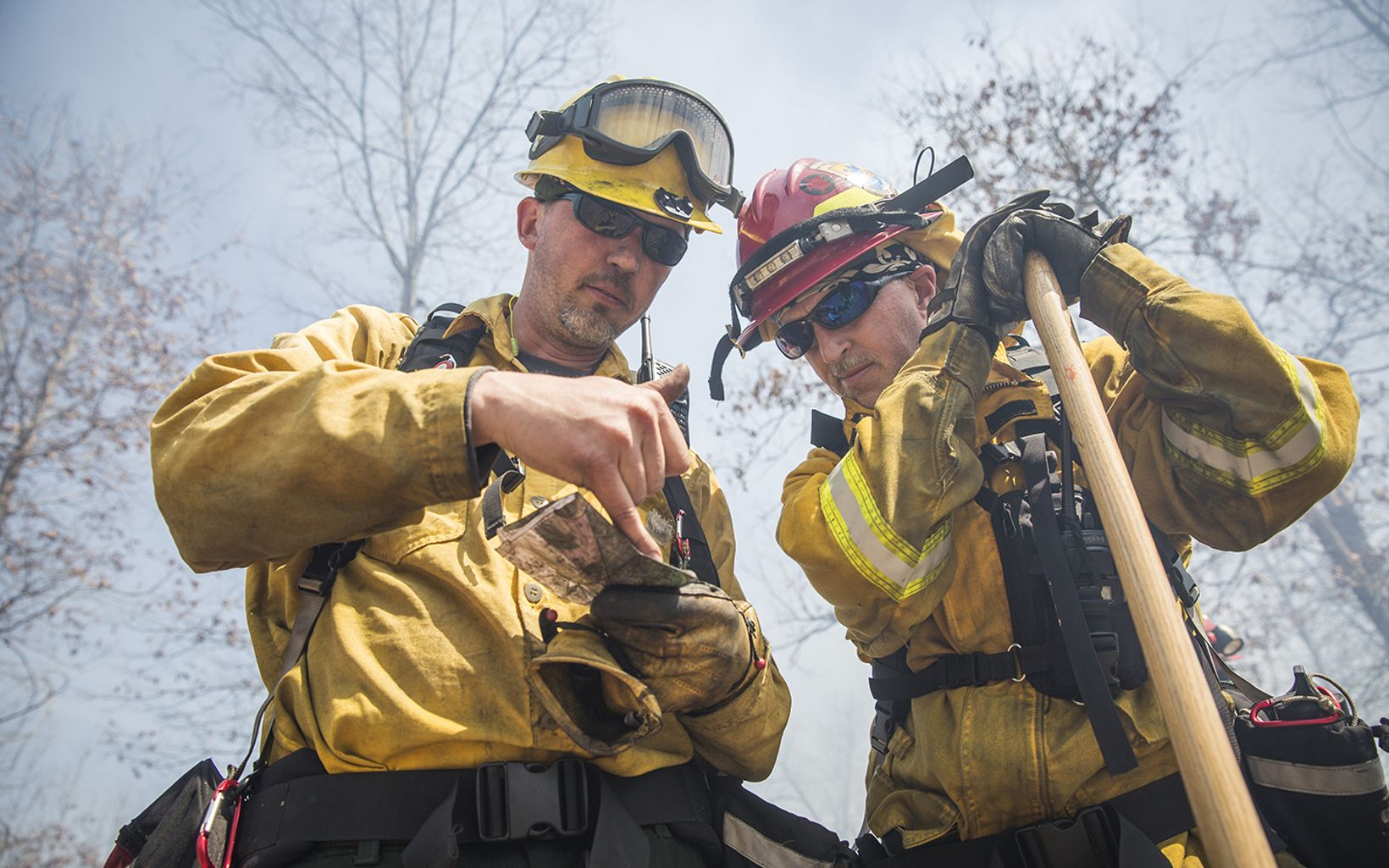 Two fire personnel look at a map.