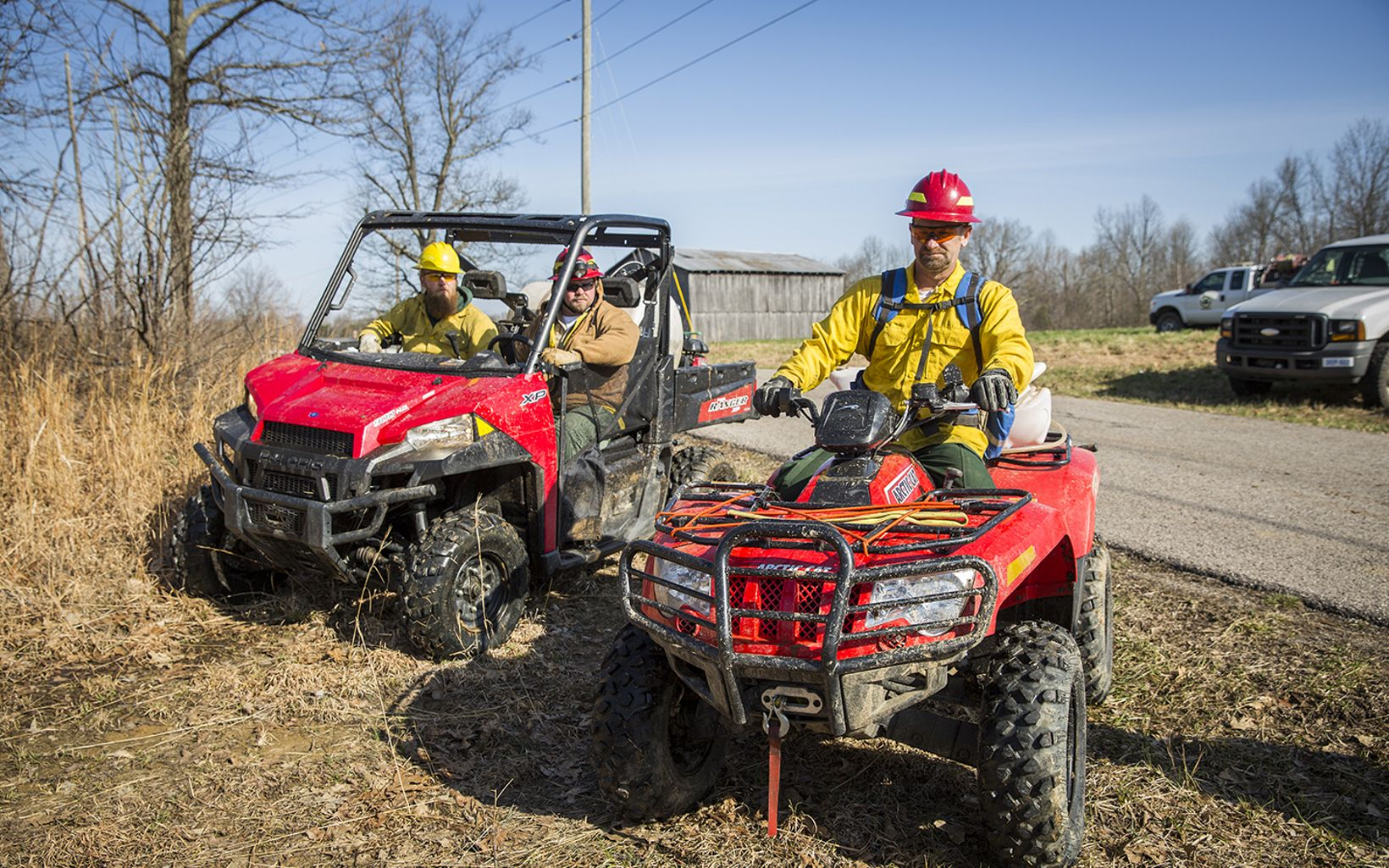 Fire personnel sit on ATVs and UTVs before a prescribed fire.