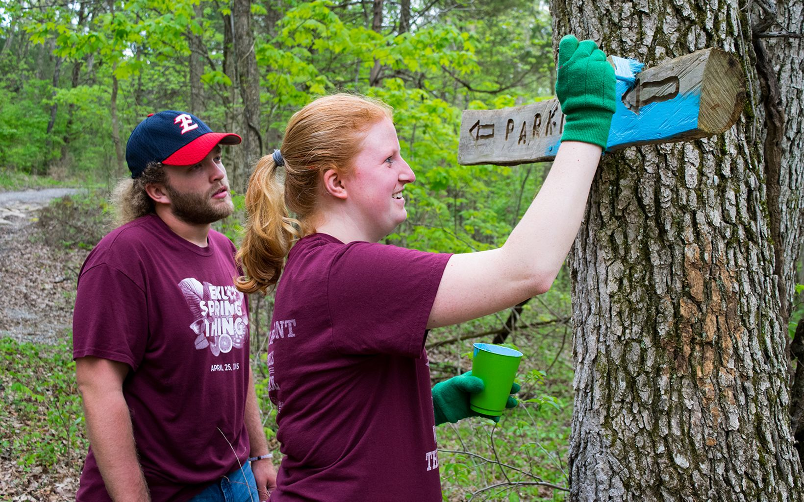 Volunteers paint a Parking sign blue attached to a tree.