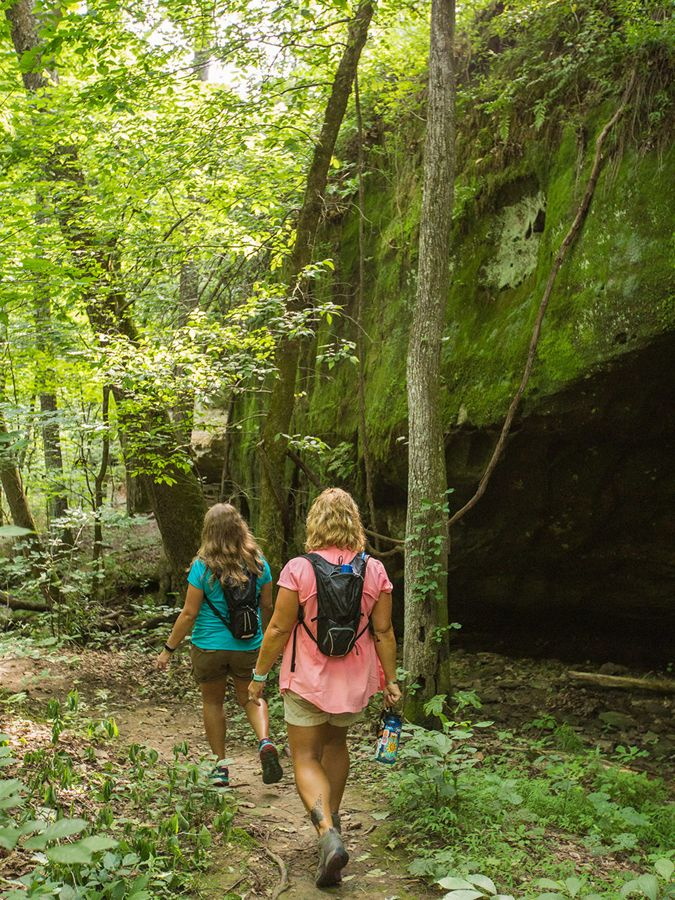 Two hikers walking a nature path next to a rock ledge.