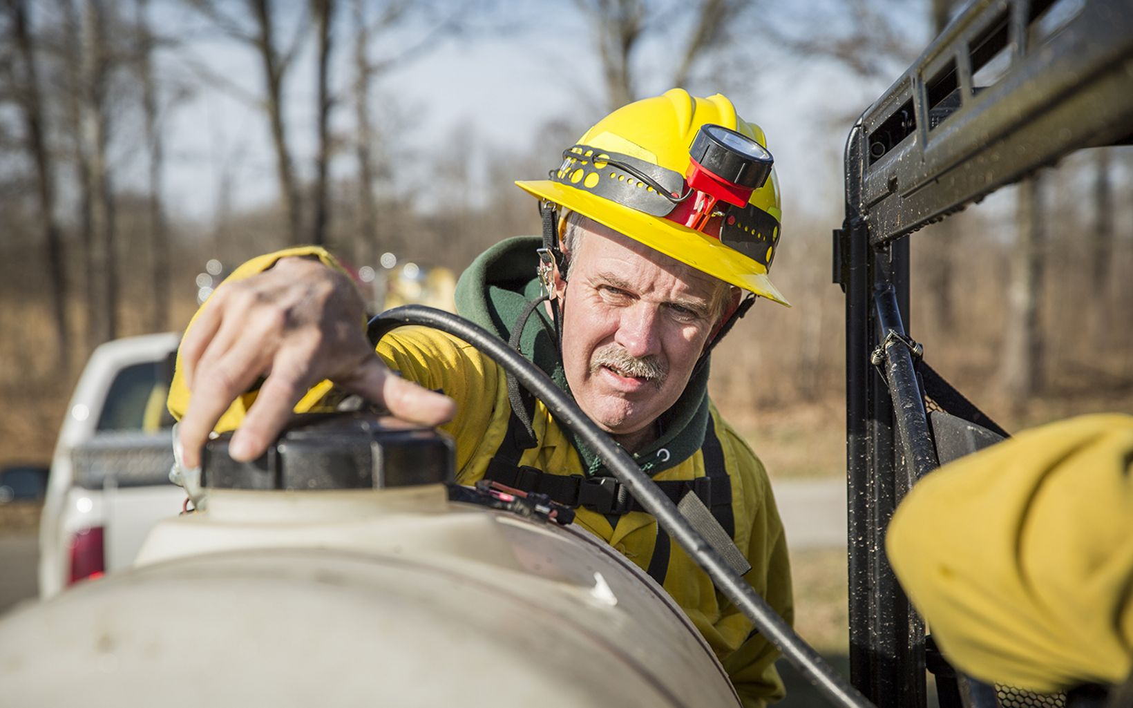 A fire worker checks a water tank before a prescribed fire.