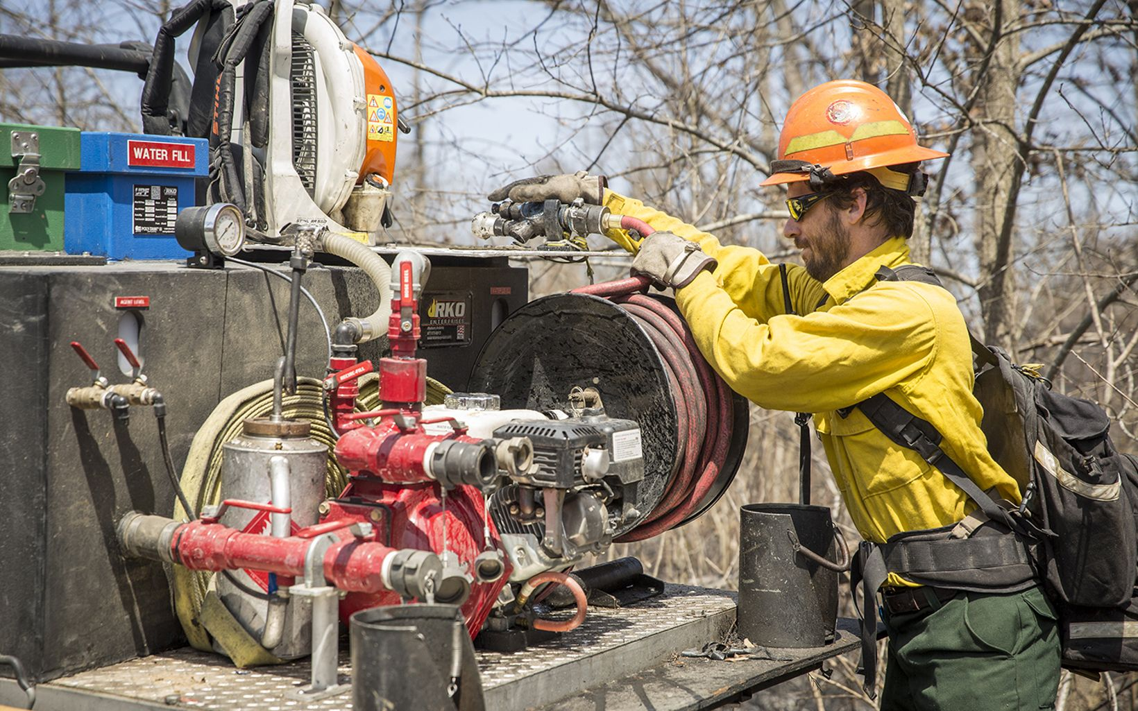 A TNC employee checks a water hose before a prescribed fire.