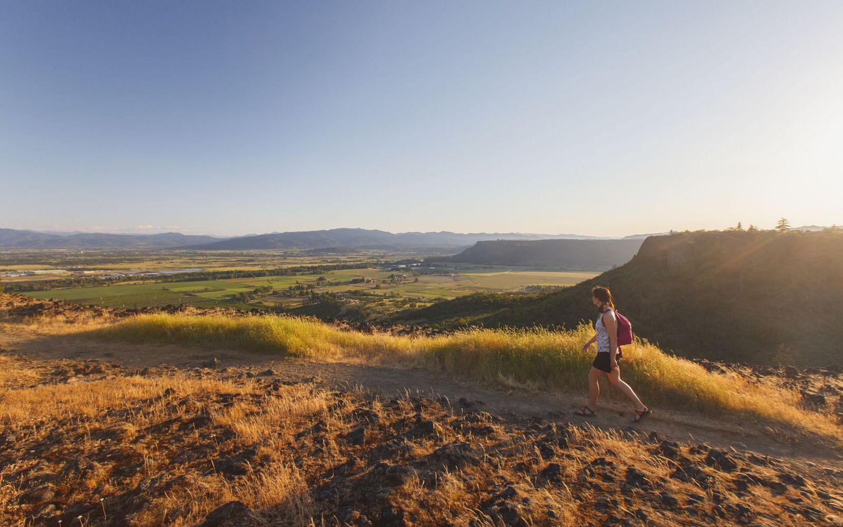 A woman hikes along the edge of Upper Table Rock overlooking the Rogue Valley at sunset, Oregon.