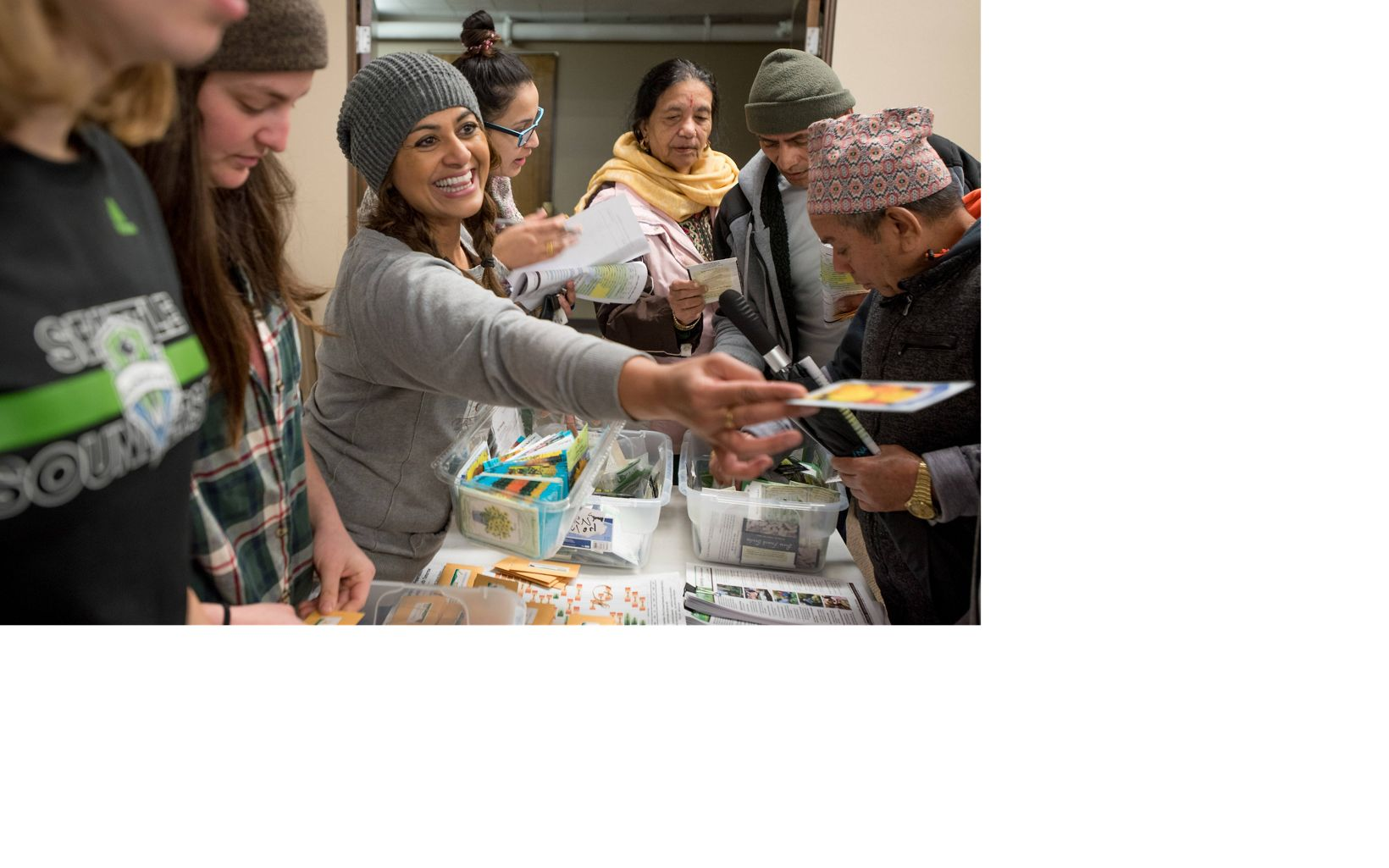 Tahmina Martelly of World Relief Seattle hands out seeds to refugees and their families.