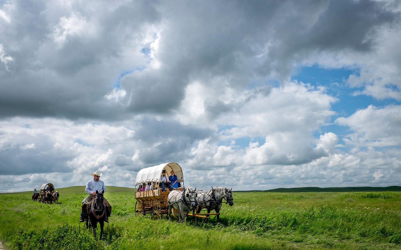 People in covered wagons pulled by horses in a vast open grassland.