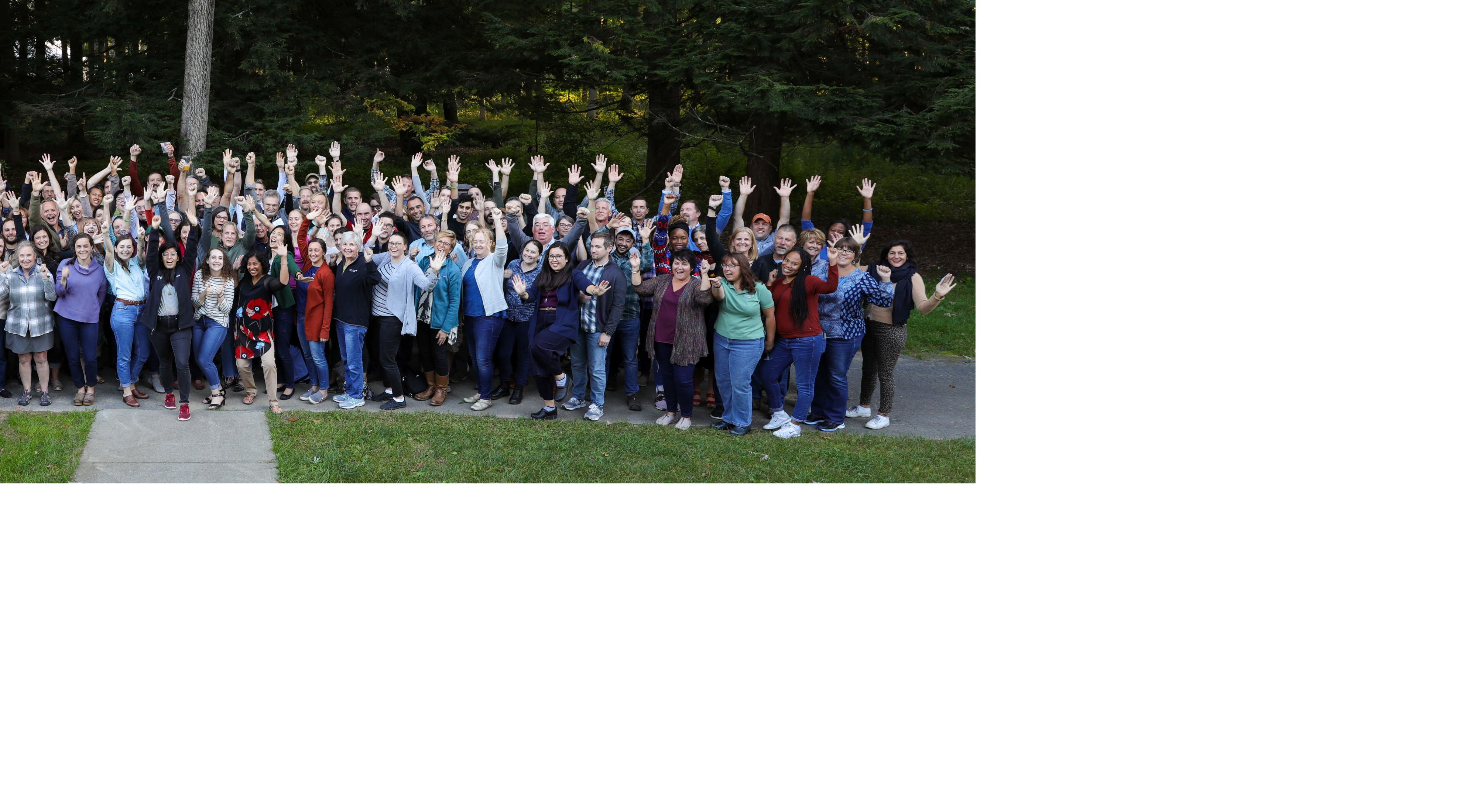 Group picture of TNC staff in an outdoor setting smiling at camera with arms raised.
