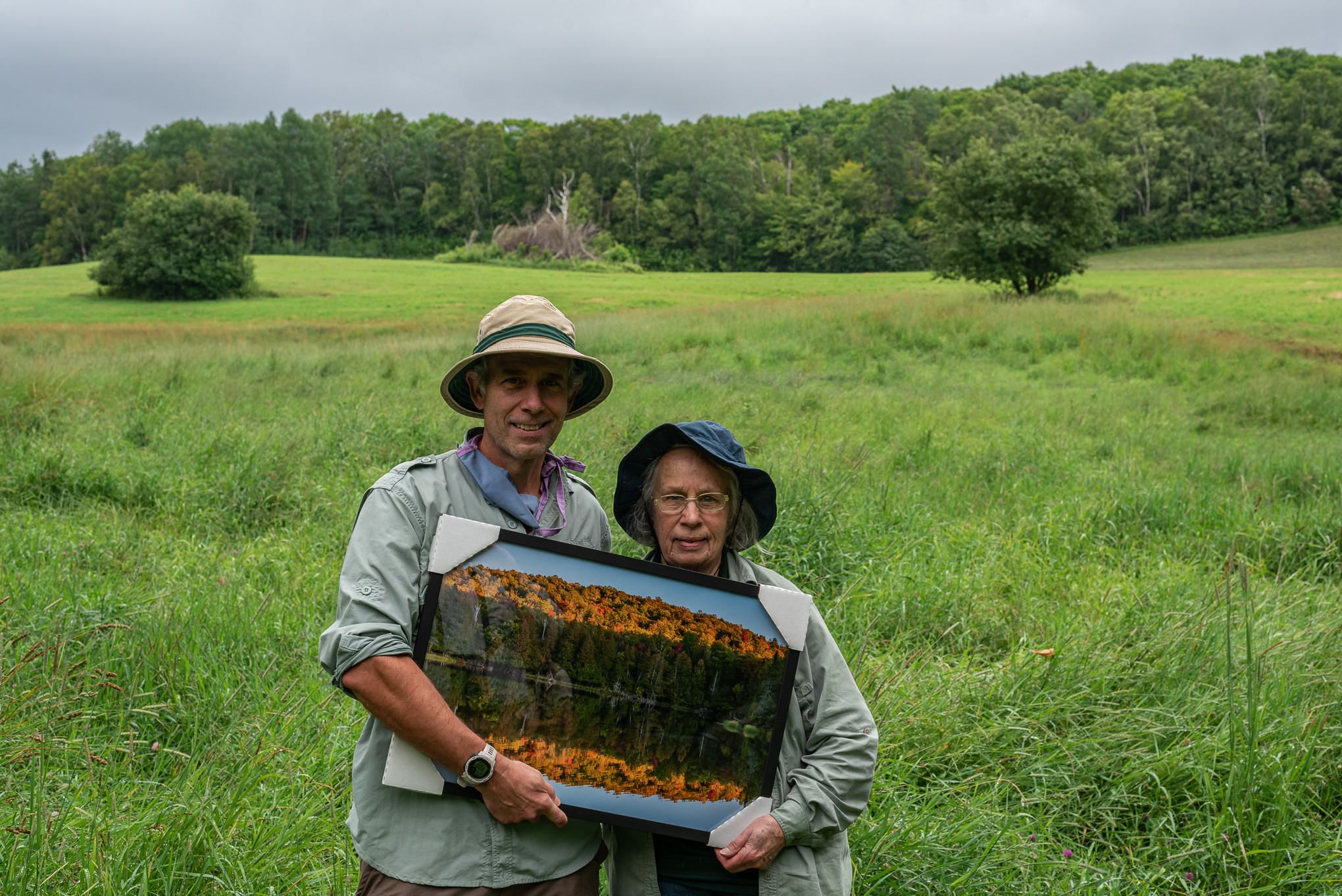 A man and woman hold a framed photo of trees.