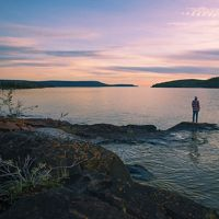 Ethan Rombough stands on a small island overlooking Christie Bay at the entry point of Thaidene Nëné National Park.