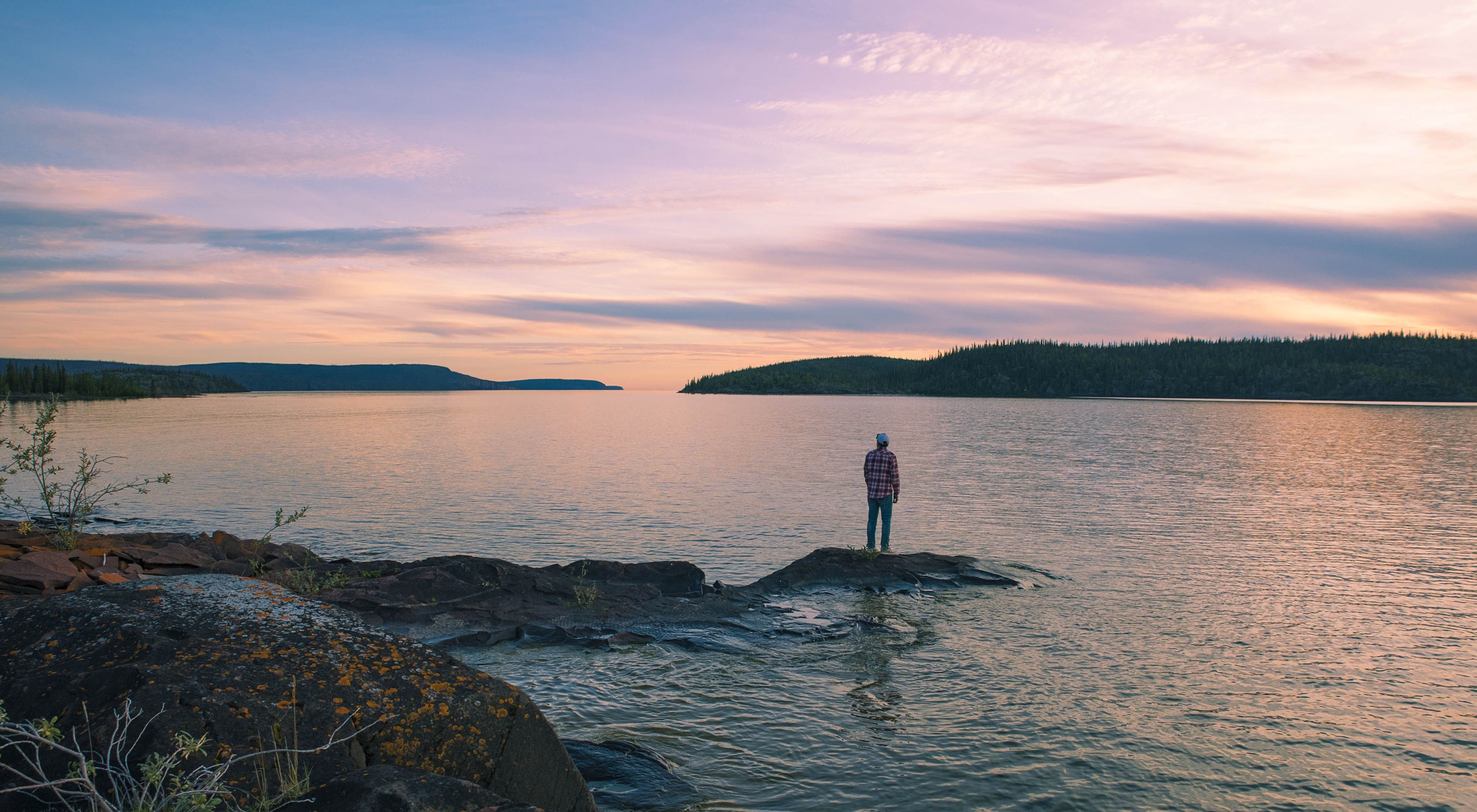 A man stands on a small island overlooking Christie Bay at sunset.