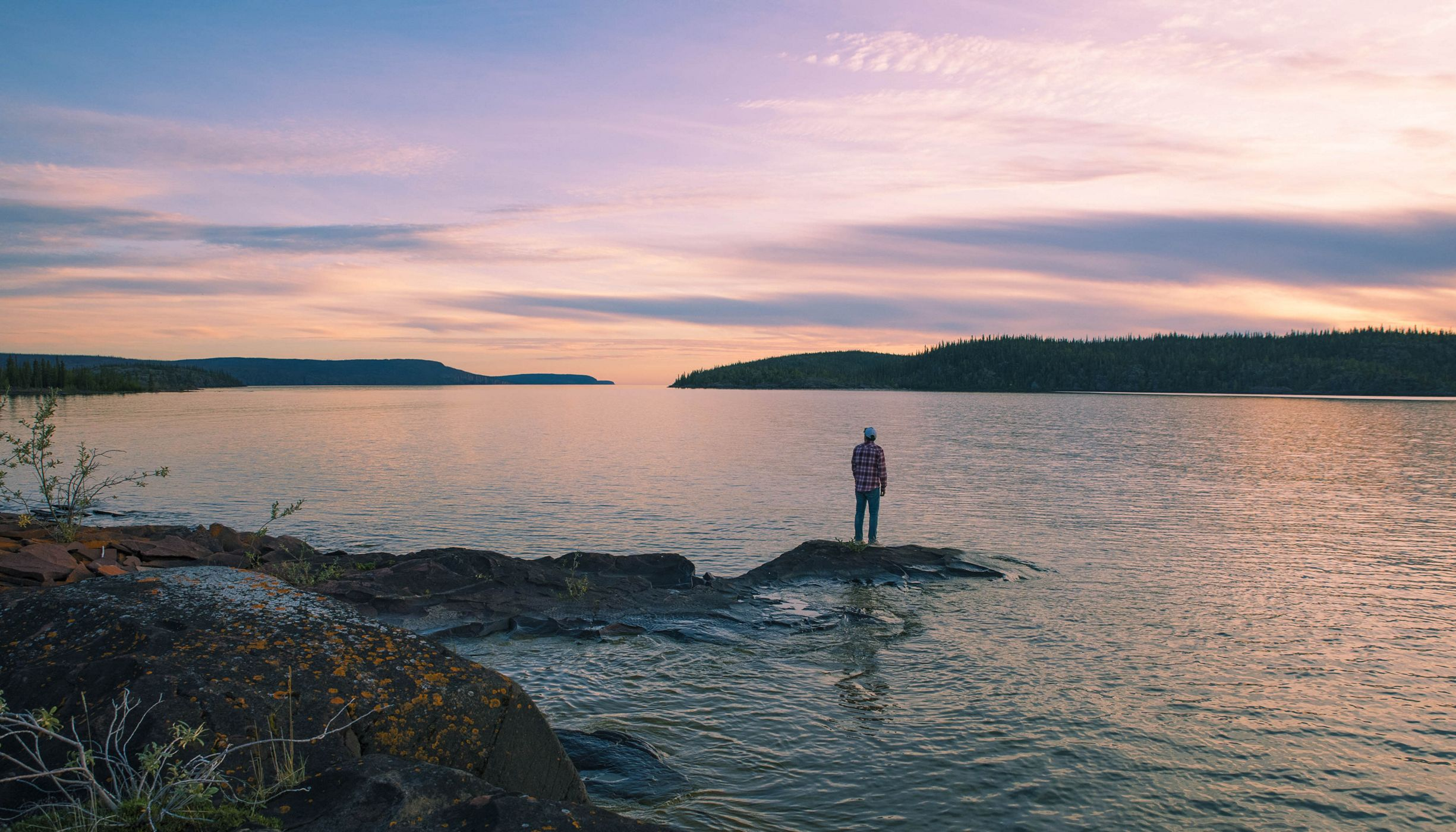 A man stands on an island in Christie Bay, one of the entry points to Thaidene Nene National Park Reserve.