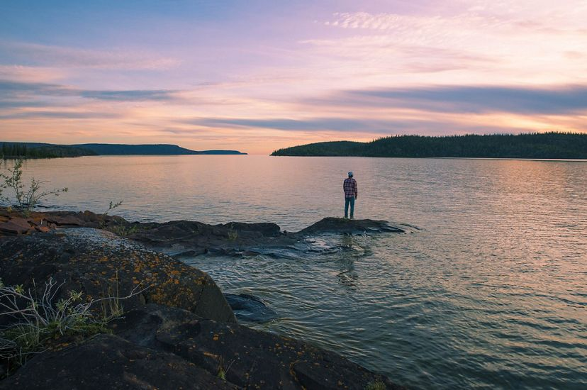 A person stands on a large piece of rock jutting out into the water in Thaidene Nene.