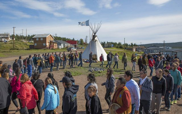 Members of the Łutsël K'é Dene First Nation dance in a large circle.