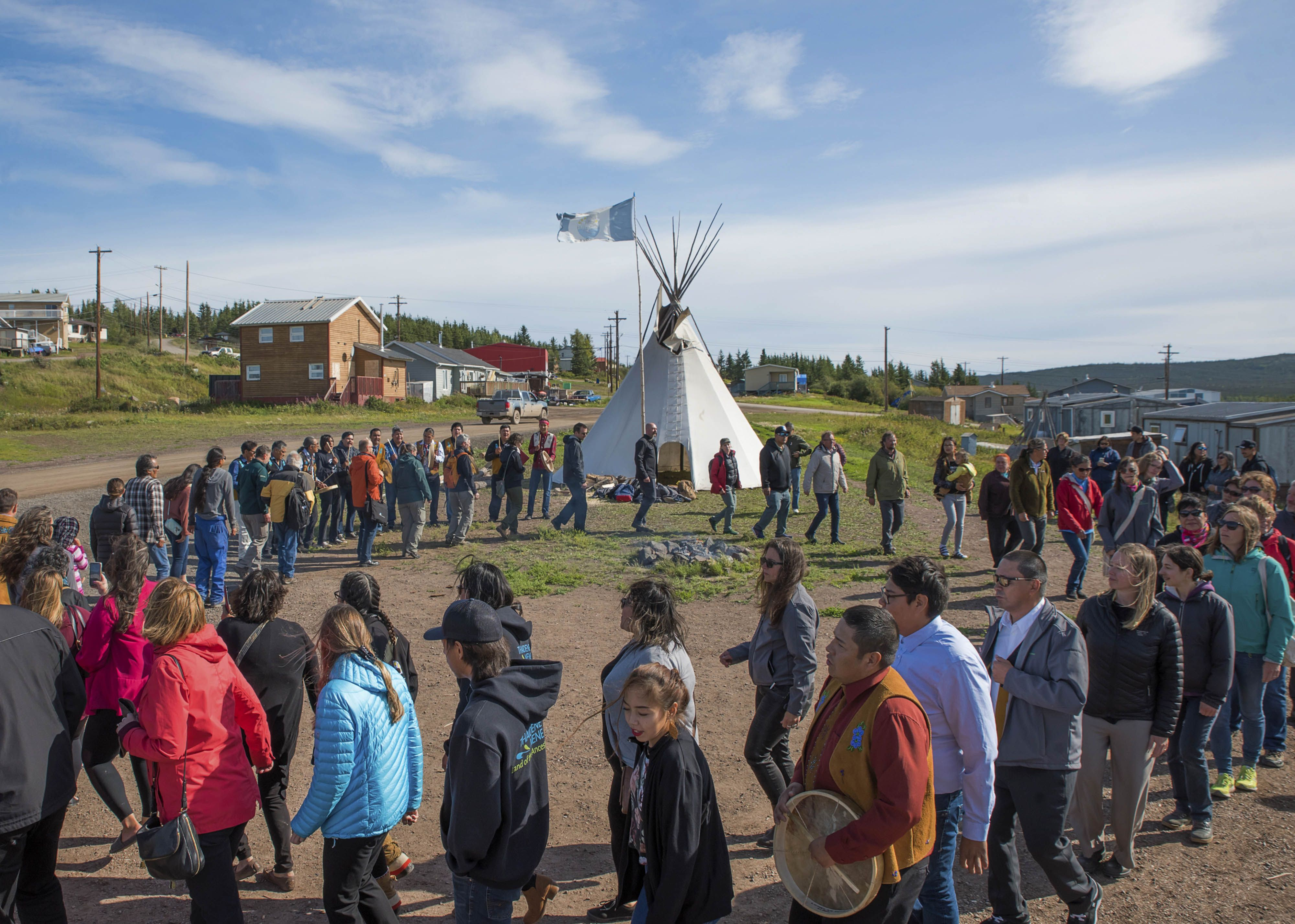 a group of people walking in a circle around a teepee structure