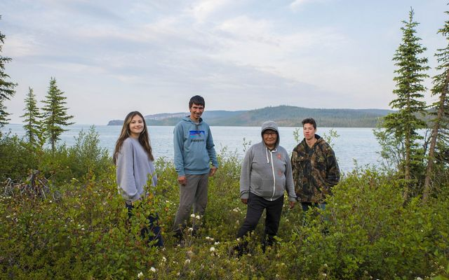 Three young people and Terri Enzoe stand amidst tall grasses with water in the background.