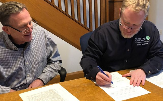 Brent Bailey (Director, West Virginia Land Trust) and Thomas Minney (Director, TNC in West Virginia) sign paperwork to transfer a 500-acre, Monroe County tract to WVLT.