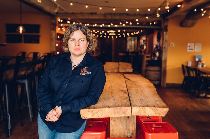 Throwback Brewery Co-Founder Nicole Carrier leans against a wooden table inside the brewery.