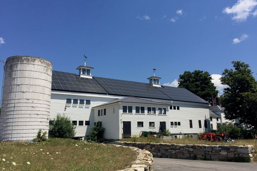 A large white barn with a roof covered in solar panels. A white silo stands to the left and a stonewall to the right.