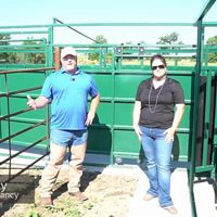 man and women standing in front of metal corral