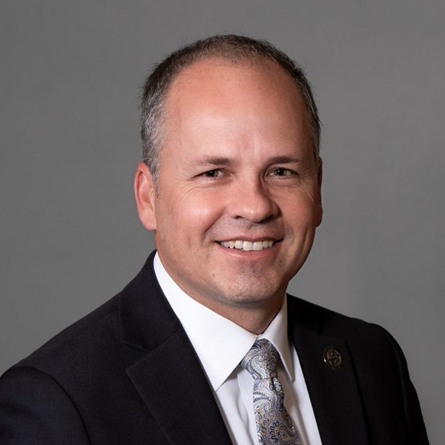 Professional photo of a man with a black suit on.