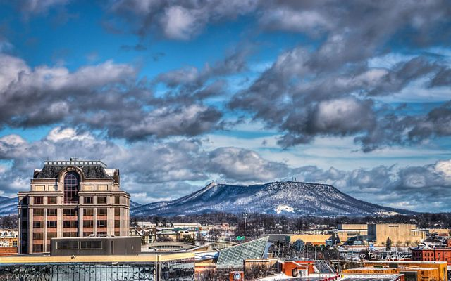 Heavy white clouds hang low over a flat-topped mountain frosted with snow that rises behind the city skyline of Roanoke, VA.