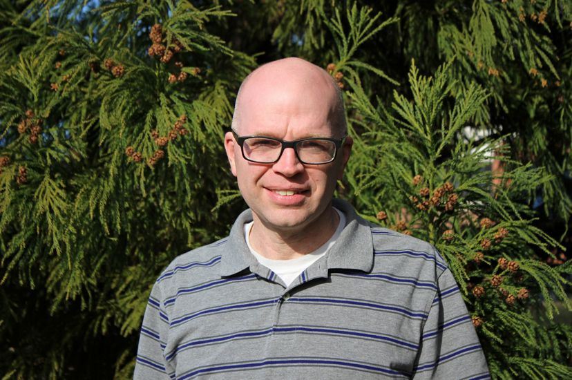 A man poses for a photo standing outside in front of an evergreen tree. He wears glasses and a gray striped sport shirt.