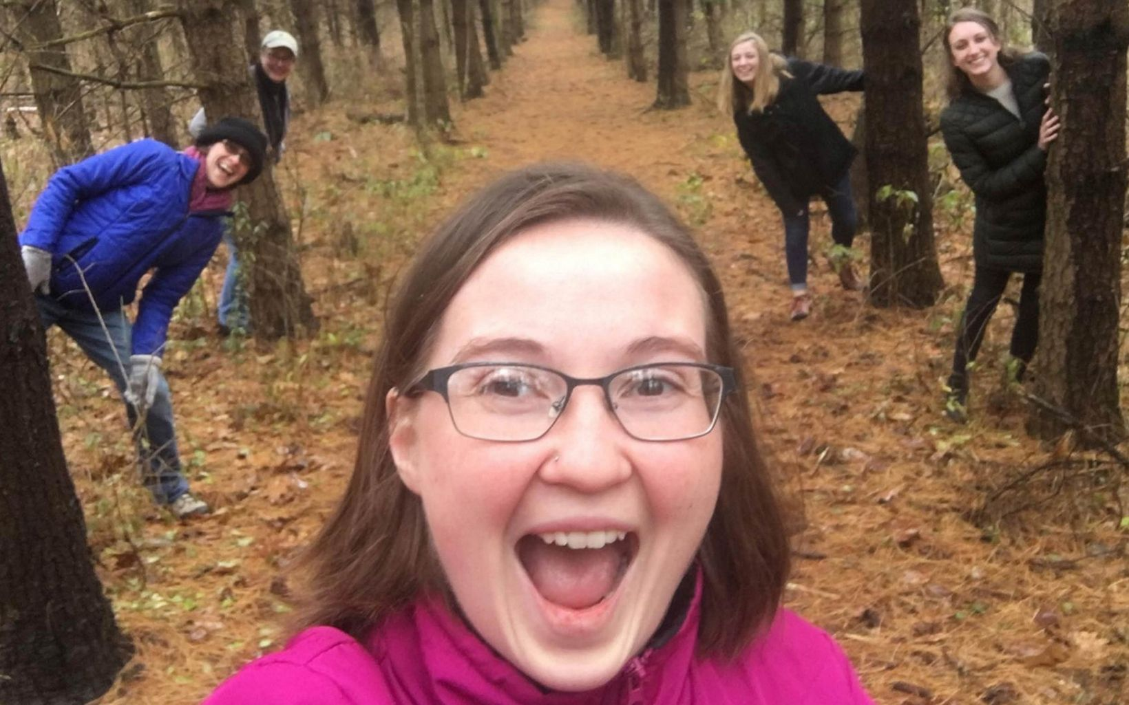 Group of women hiding behind trees on a nature trail.