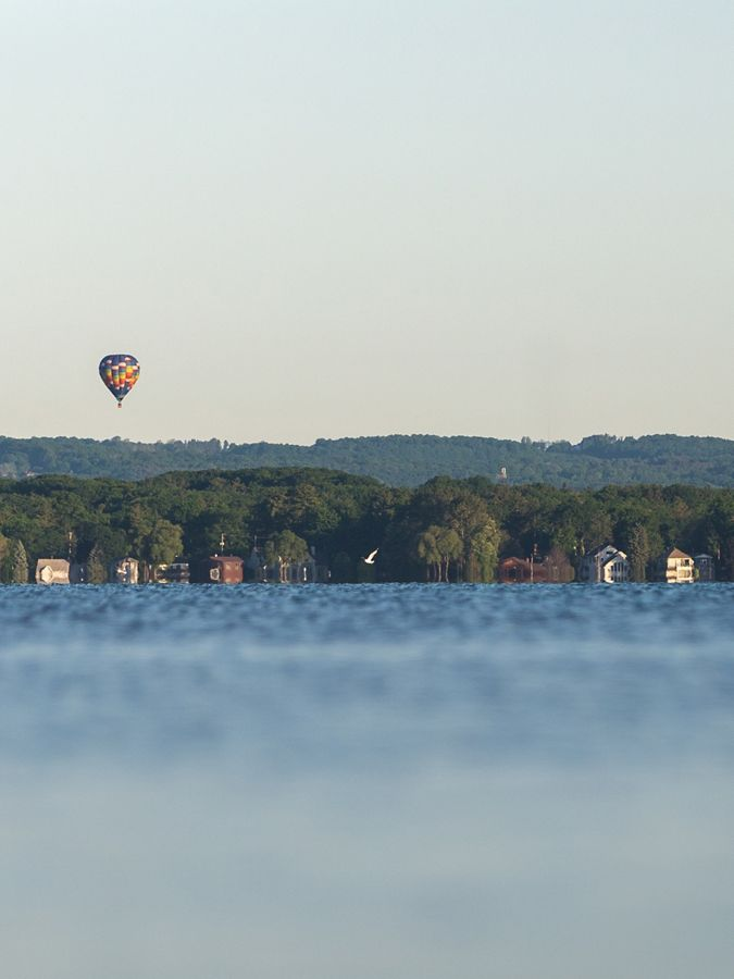Hot air balloon in light sky over blue water.